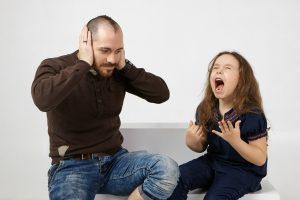 Niña gritando y padre tapándose los oídos
